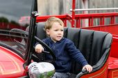 picture of steers  - A happy young boy sits in an old shiny vintage red fire truck holding on to the steering wheel looking out - JPG