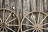 foto of wagon wheel  - A close up of two vintage wagon wheels lying up against a building - JPG