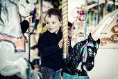 picture of amusement park rides  - A happy young boy sits on a horse on a carousel ride in an amusement park - JPG