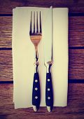 Fork, knife and napkin on wooden restaurant table, toned image