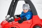 foto of cold-weather  - A young boy dressed for cold weather with a serious expression sits in a red toy car stuck in the snow during the winter season - JPG