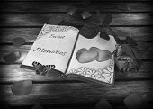 nostalgia - book, rose and butterflies on wooden table