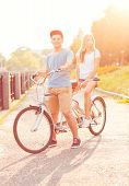 Young Man And Woman Riding A Bicycle In The Park Outdoors