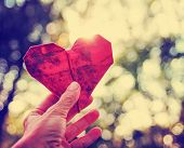 a hand holding an origami paper heart up to the sun during sunset toned with a vintage retro instagram filter effect