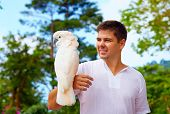 Young Man Holding Gorgeous Cockatoo Parrot