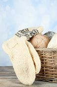 Knitting yarn and socks in basket, on light background