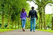 Couple Holding Hands And Walking In A Park