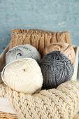 Knitting yarn in basket, on wooden background