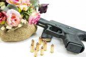 handgun pistol and flower on white and blurred background.