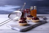 Delicious cookies with jam and powdered sugar on cutting board on wooden background