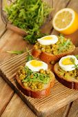 Sandwiches with green peas paste and boiled egg with herbs and lemon on wooden planks background