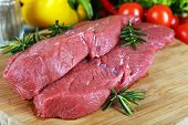 Raw beef steak on cutting board with vegetables and greens on table close up