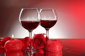 Composition with red wine in glasses, red rose and decorative heart on colorful background