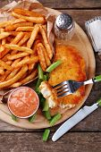 Breaded fried fish fillet and potatoes with asparagus and sauce on cutting board and rustic wooden background