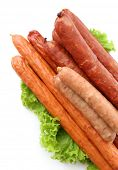 Assortment of thin sausages  with lettuce salad leaves, isolated on white
