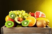 Assortment of fruits in box on dark yellow background