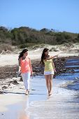 Young Female Friends Strolling At The Beach