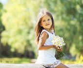 Sunny Little Girl With A Bouquet Of Chamomiles Flowers In Spring Day