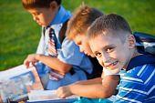 foto of school child  - Lovely kids with books sitting in park - JPG