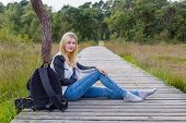 Blonde girl sitting on wooden path in nature