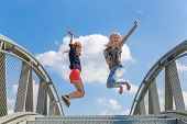 picture of enthusiastic  - Two enthusiastic girls jumping on bridge in front of blue sky and white cloud - JPG