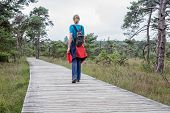 Woman hiking on wooden path in nature
