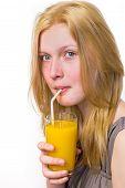 Blonde girl drinking orange juice with straw
