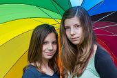 Two caucasian teenage girls under colorful umbrella