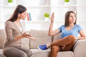 picture of adolescent  - Teen girl is showing stop gesture to angry mother while sitting on sofa at home - JPG
