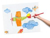 airplane on checkered paper. children drawing hand with crayon.