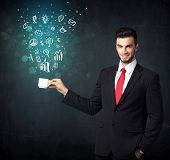 Businessman standing and holding a white cup with business icons coming out of the cup