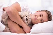 Young man lying under a blanket with teddy bear