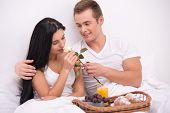 stock photo of early 20s  - Young couple sitting under white blanket early in the morning and having their breakfast in bed - JPG