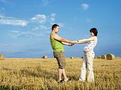 Young Pregnant Woman With Husband In The Meadow