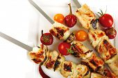 fresh grilled chicken shish kebab on white platter