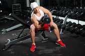 Power athletic guy bodybuilder, execute exercise with dumbbells