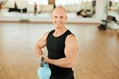 Young muscular man doing exercise with kettlebell