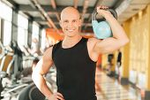 Confident smiling man with kettlebell at fitness gym