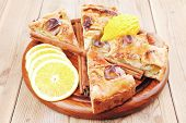 baked food : apple pie cuts on over table with cinnamon sticks and lemons