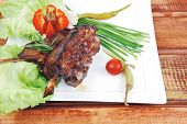 savory plate over wooden table: grilled ribs on white plate with chives, red hot peppers lettuce