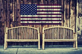 stock photo of sitting a bench  - Two rustic wooden log benches sit side by side outdoor against a building wall made of wooden siding with a USA flag hanging on the wall just above the benches - JPG
