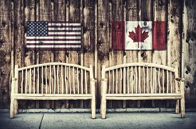 stock photo of sitting a bench  - Two rustic wooden log benches sit side by side outdoor against a building wall made of wooden siding with a USA and Canada flag hanging on the wall just above the benches - JPG