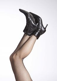 stock photo of fishnet stockings  - legs with fishnet stocking and high heels boots - JPG