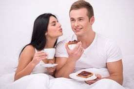 picture of early 20s  - Young couple sitting under white blanket early in the morning and having their breakfast in bed - JPG
