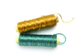 pic of rayon  - metallic rayon thread line spool in green and golden colors over white - JPG