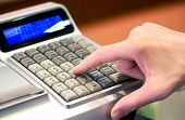 picture of cash register  - Close up of the hand of a person entering a sale on a cash register punching in the amount on the key pad with a view of the digital readout - JPG
