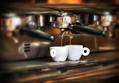 stock photo of dispenser  - Italian espresso machine on a counter in a restaurant dispensing freshly brewed coffee into two small cups to be served to customers