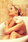 picture of bath sponge  - Woman relaxing in a bath and washing herself by sponge - JPG