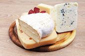 stock photo of cheese platter  - edam parmesan and brie cheese on wooden platter over wooden table - JPG