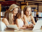 stock photo of mums  - Little girls and their mum with a laptop in library - JPG